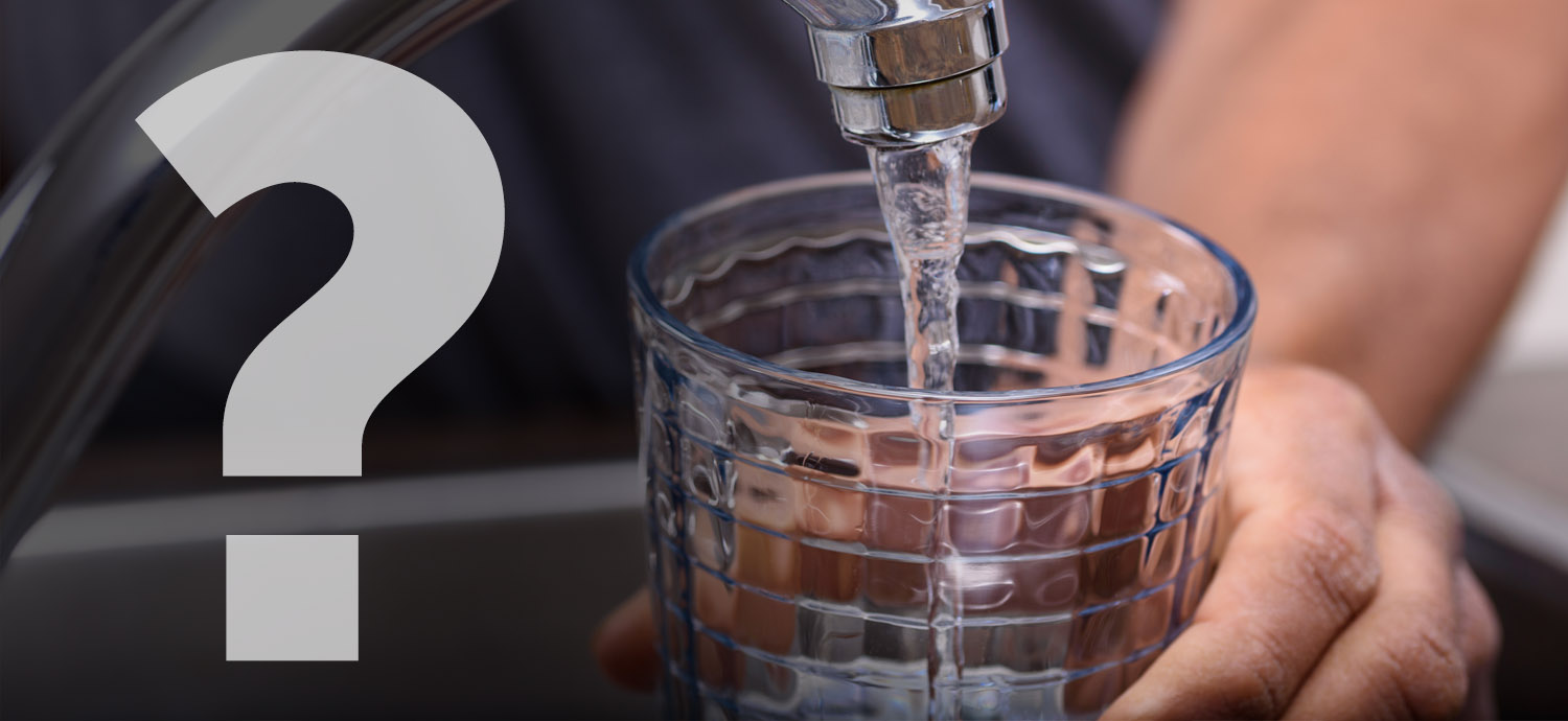Question mark over closeup of man filling glass from tap