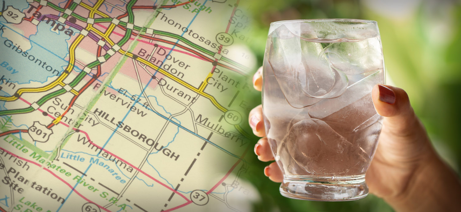 Hand holding water glass over map of Hillsborough County, Florida